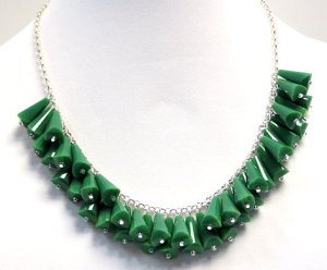 These green components, in the piece shown above, are made out of Chinese crystal, not plastic.     To the naked eye, you might see a similar piece where the components are plastic, looking like but definitely not crystal.   The eye can deceive itself.   Simple test: click bead against a stiff surface or front teeth.   If crystal or glass, you will hear a sharp click; if plastic, you will hear a dull click.